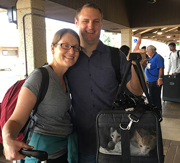Couple with two cats in carrier at Lihue airport